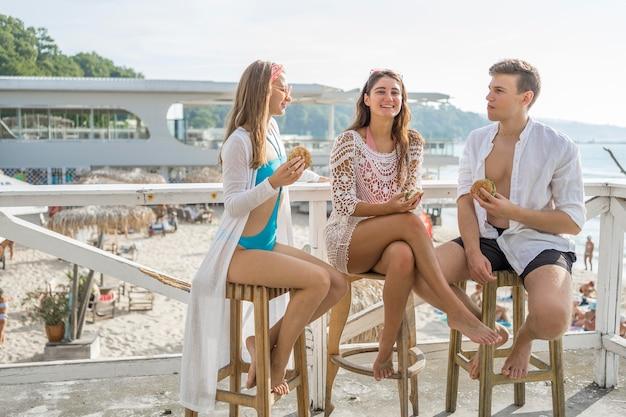 Tres amigos disfrutando de hamburguesas juntos en la playa.