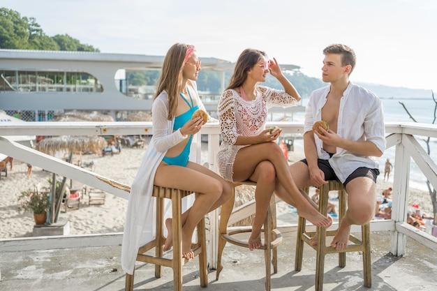 Tres amigos disfrutando juntos de hamburguesas en la playa
