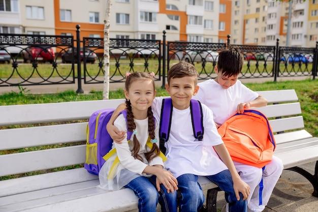 Tres amigos de la escuela, 1 niña y 2 niños, se sientan en un banco con mochilas brillantes y miran en el marco