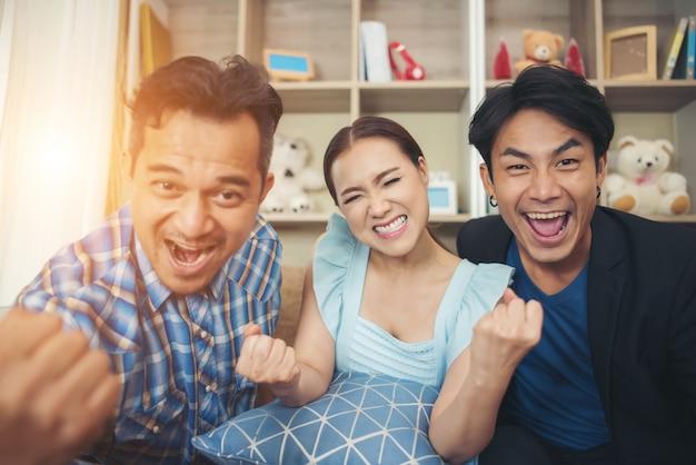Tres amigos están muy contentos después de ver la televisión.