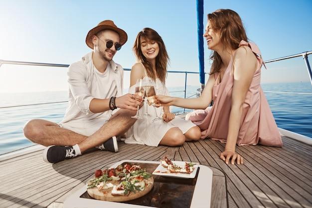 Tres amigos europeos de moda sentados en el barco, almorzando y bebiendo champán, expresando alegría y placer. cada año reservan entradas para países cálidos en invierno