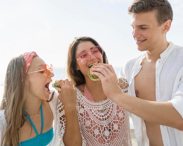 Tres amigos felices al aire libre comiendo hamburguesas juntos