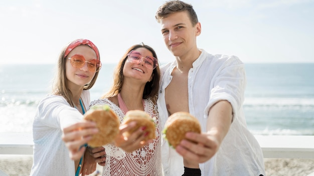 Tres amigos felices al aire libre con hamburguesas