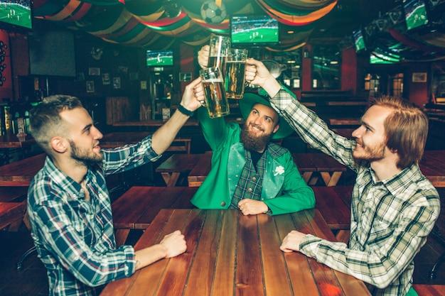 Tres amigos jovenes felices que sostienen las tazas de cerveza juntas sobre la tabla en pub. la gente sonríe el chico del medio usa el traje verde de san patricio.