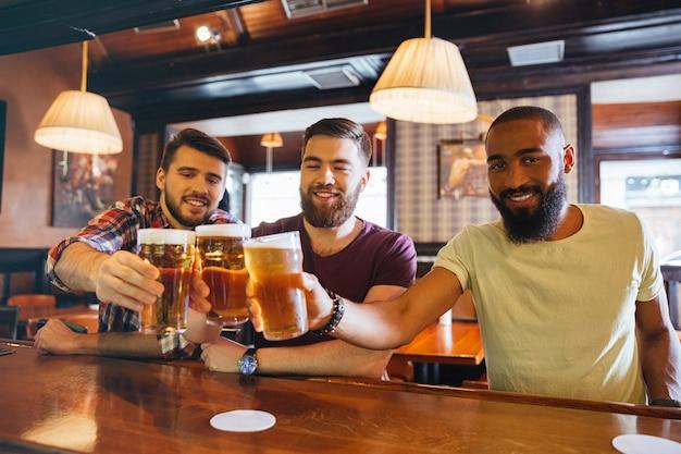Tres amigos jóvenes guapos sonrientes bebiendo cerveza en el bar juntos