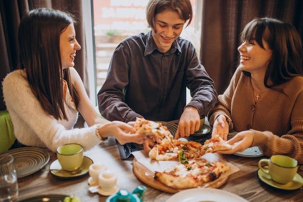Tres amigos juntos comiendo pizza en un café