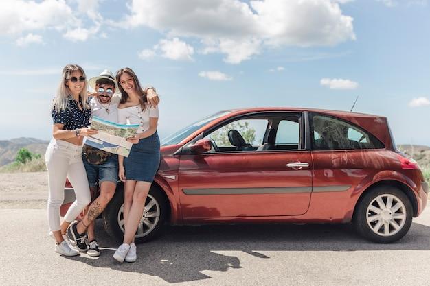 Tres amigos con mapa de pie cerca del coche moderno en la carretera