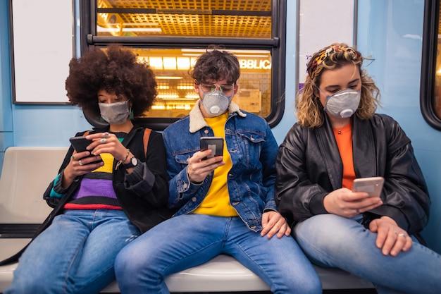 Tres amigos multiétnicos con una máscara médica que protege contra la contaminación y los virus en el metro usando un teléfono inteligente