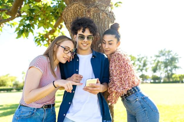 Tres amigos que se divierten con el teléfono inteligente en el parque señalando y enviando mensajes de texto en la pantalla.