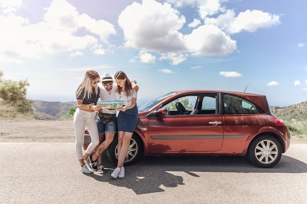 Tres amigos que miran el mapa que se coloca cerca del coche moderno en el camino