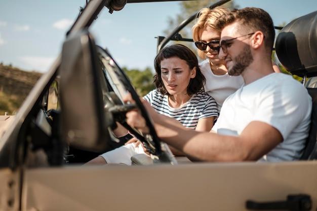Tres amigos revisando el mapa mientras viaja en coche