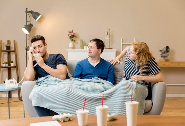 Tres amigos en el sofá con mantas y vasos de refresco