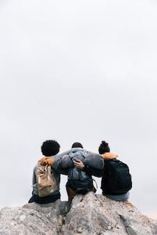 Tres amigos con sus brazos alrededor sentados en la cima de la montaña