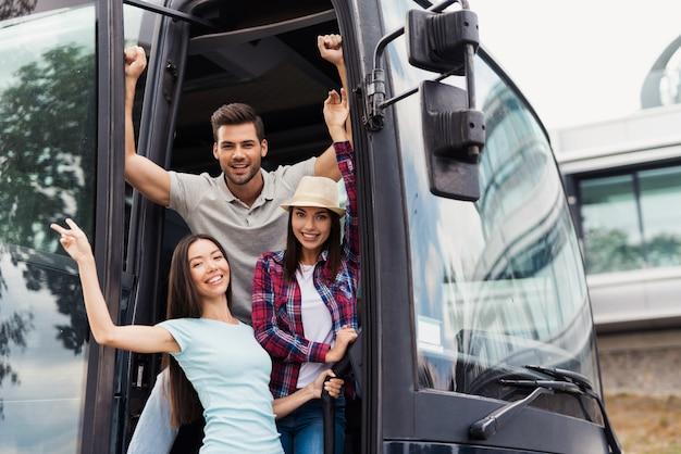 Tres amigos de turistas se asoman por las puertas del autobús.