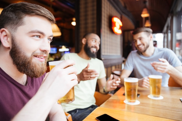 Tres amigos varones felices bebiendo cerveza en el pub