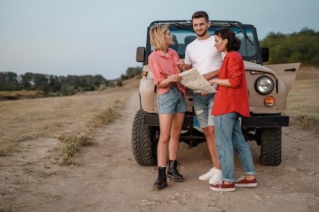 Tres amigos viajando en coche y comprobando el mapa.