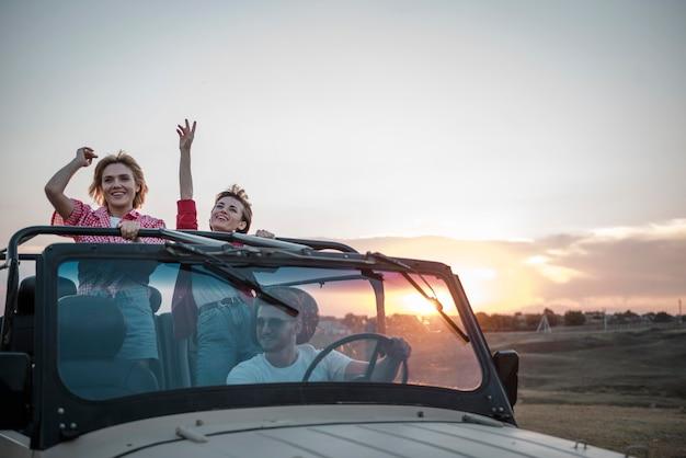 Tres amigos viajando en coche y divirtiéndose.