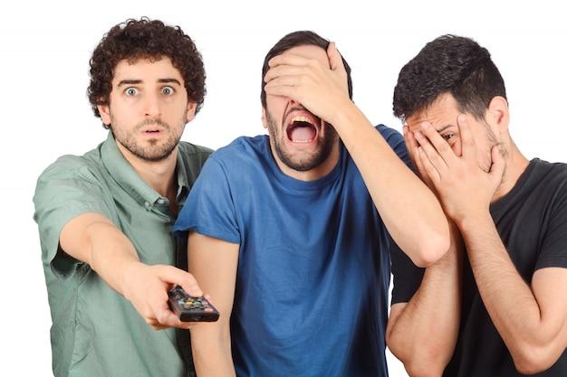Tres amigos viendo una película.