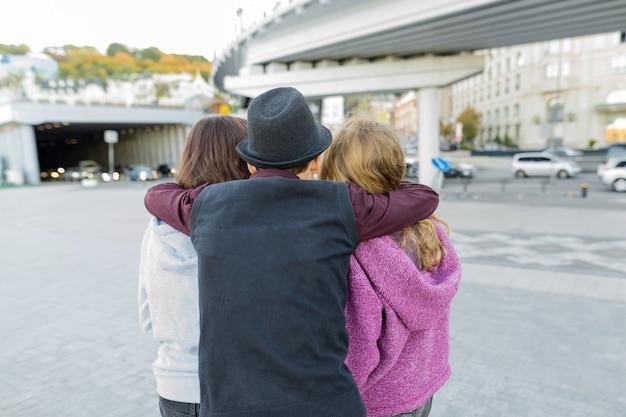 Tres amigos, vista desde la parte posterior del niño abrazando a dos niñas