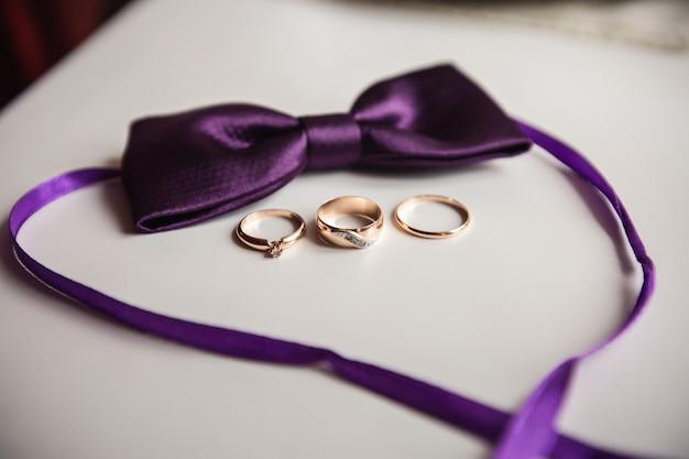Tres anillos de boda: uno para la novia, uno para el novio y un anillo de propuesta cerca de la pajarita morada