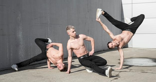 Tres artistas de hip hop bailando practicando afuera