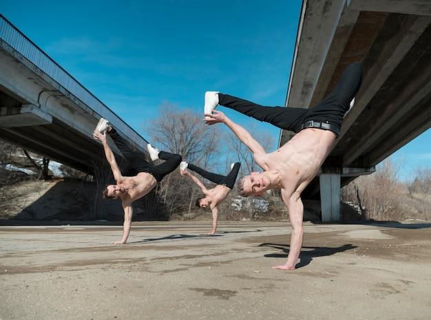 Tres artistas de hip hop sin camisa que practican la rutina de baile afuera