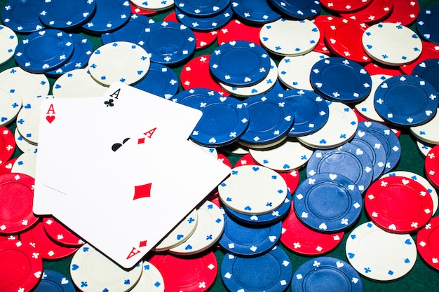Tres ases tarjeta sobre el blanco; fichas de casino azul y rojo