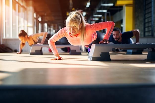 Tres atletas jóvenes fuertes haciendo algunas flexiones con una mano en un stepper.