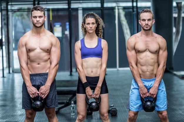 Tres atletas musculares levantando una campana caldera