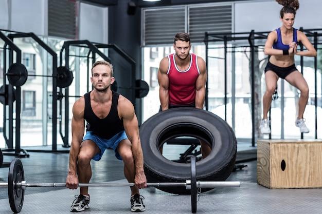 Tres atletas musculares levantando y saltando