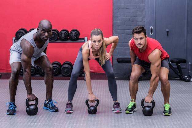 Tres atletas musculares a punto de levantar una campana caldera
