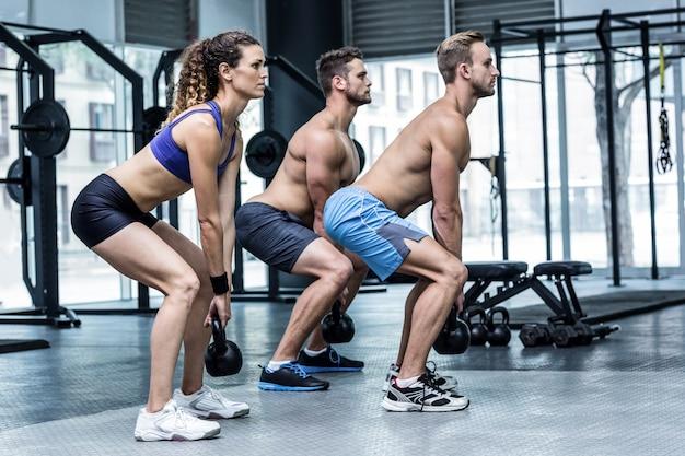 Tres atletas musculosos en cuclillas juntos