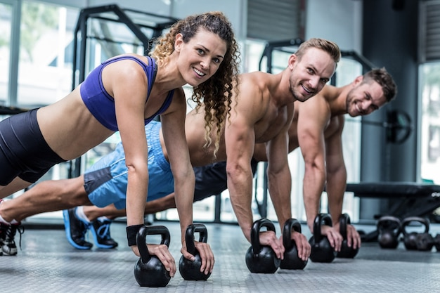 Tres atletas musculosos en una posición de tabla