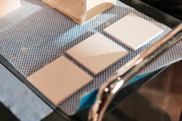 Tres azulejos cerámicos pintados en mesa.
