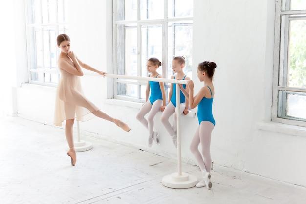 Tres bailarinas bailando con profesora de ballet personal en estudio de danza