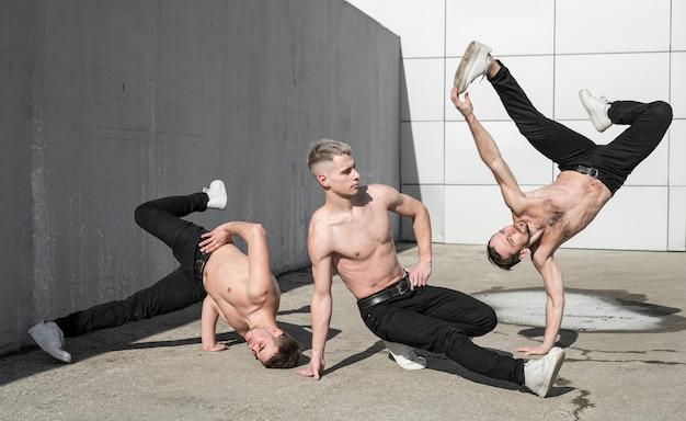 Tres bailarines de hip hop sin camisa afuera