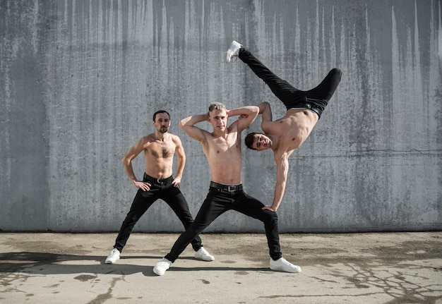 Tres bailarines de hip hop sin camisa posando juntos