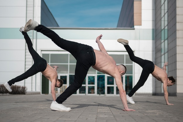 Tres bailarines de hip hop sin camisa practicando afuera