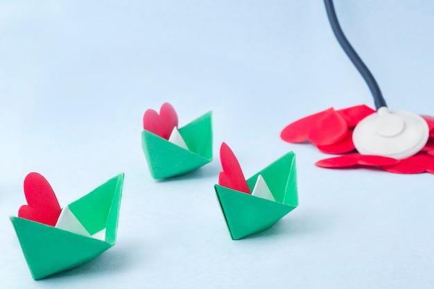 Tres barcos de papel verde con corazones rojos.