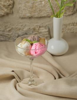 Tres bolas de helado con café, vainilla y fresa en vaso de cristal.
