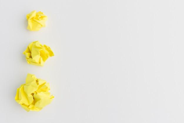 Tres bolas de papel arrugado amarillo de diferentes tamaños contra el fondo blanco.