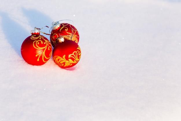 Tres bolas rojas de navidad en la nieve