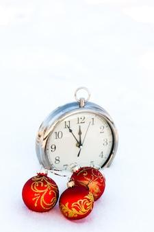 Tres bolas rojas de navidad y reloj en la nieve
