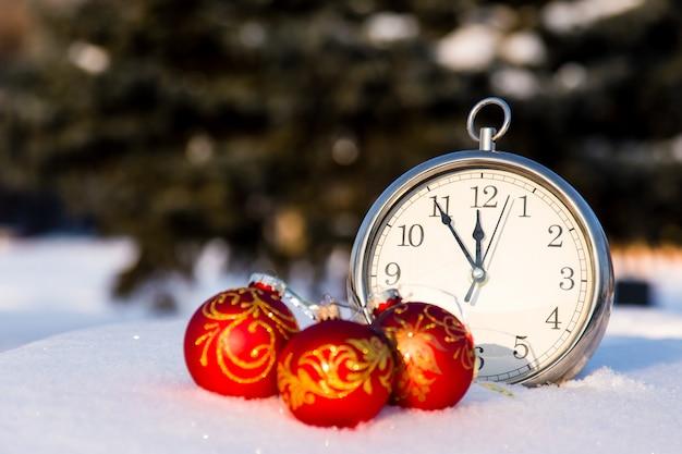Tres bolas rojas de la navidad y wath en una nieve.