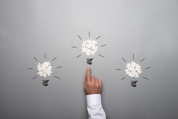Tres bombillas formadas por piezas de rompecabezas blancas dispersas con la mano de un empresario