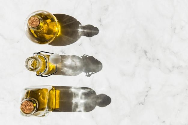 Tres botellas de aceite de oliva virgen saludable con sombra en el piso
