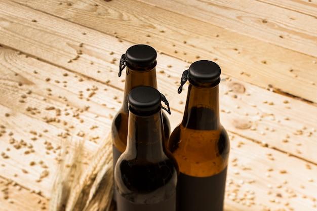Tres botellas de cerveza cerradas y espigas de trigo en madera.