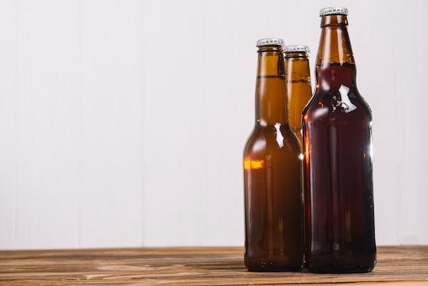 Tres botellas de cerveza en el escritorio de madera