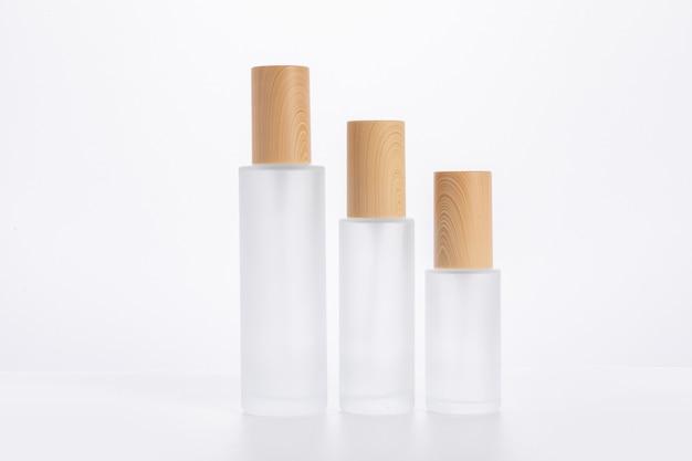 Tres botellas de cuidado de la piel de diferentes tamaños aisladas sobre una superficie blanca