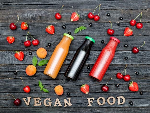 Tres botellas de jugo, comida vegana con inscripción y fruta. fondo de madera
